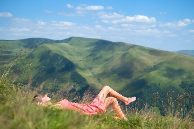 young-woman-red-dress-lying-down-green-grassy-field-resting-sunny-day-summer-mountains-enjoying-view-nature_127089-11702.jpg